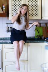 junge frau in der küche telefoniert