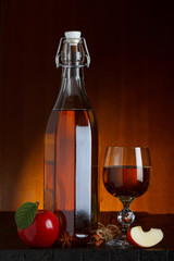 Cider bottle and glass with apple, cinnamon and anise star