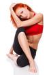 slim redhead girl sitting on white floor