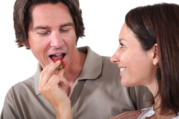 Woman offering piece of fruit to man