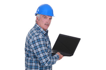 senior craftsman holding a laptop
