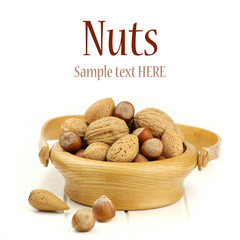 Wooden bowl of mixed nuts in shells on white background