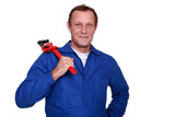 portrait of mature plumber holding adjustable spanner