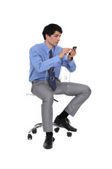 Businessman sat on chair sending SMS
