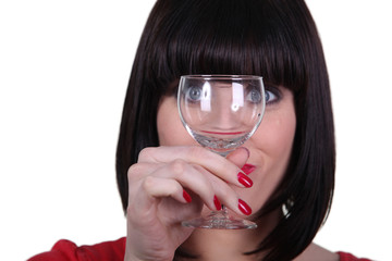 Woman watching meticulously an empty goblet
