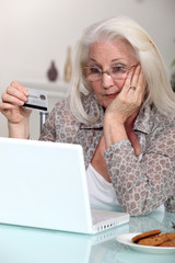 Old woman with credit card and computer