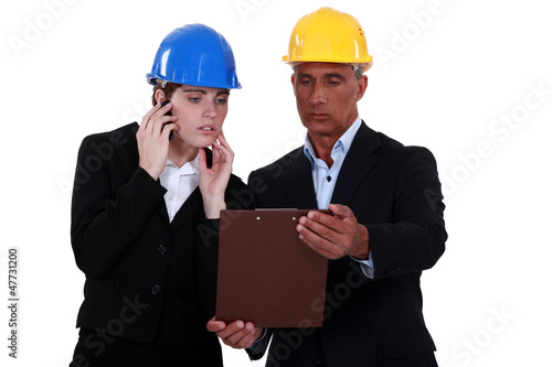Architect and colleague looking at clip-board
