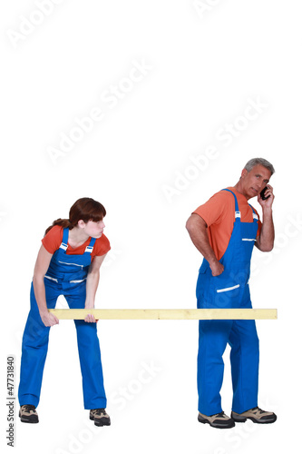 Two workers carrying wood