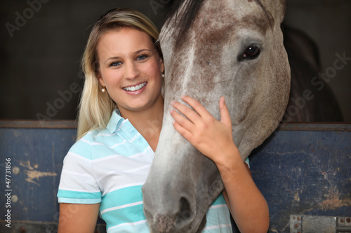 Blonde girl stroking horse