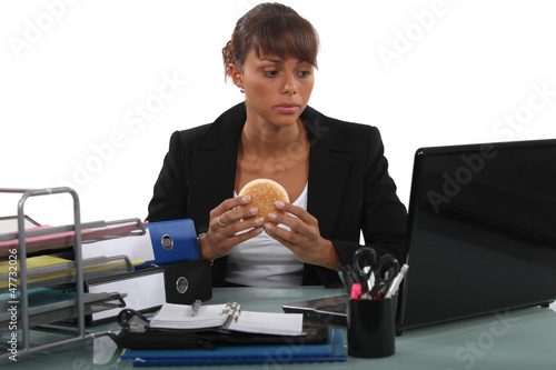 Woman eating a hamburger at her desk