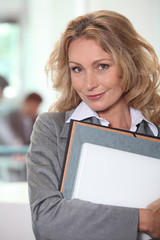 Blond office worker stood with folders