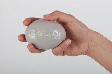 Hand holding soap marked 'natural'