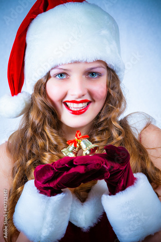 Beautiful woman in a red dress and hat of Santa with a christmas