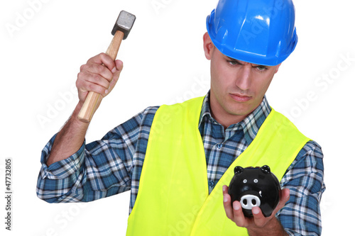 Manual worker smashing piggy-bank