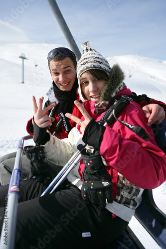 Young couple riding a ski lift