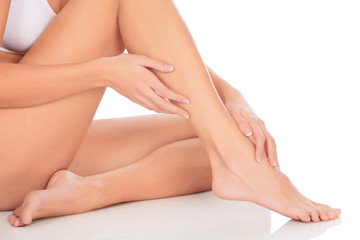 healthy naked woman legs and hands over white background
