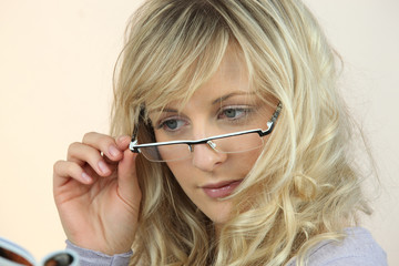 Young woman peering over her glasses at a magazine