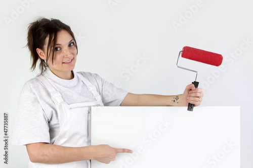 Female decorator pointing at blank poster