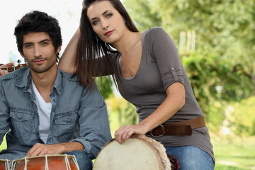 Couple playing bongo drums outdoors