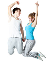 The young couple is jumping in a studio