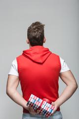 Mann hällt ein Geschenk hinter dem Rücken