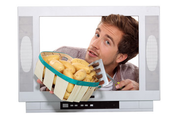 Man with potatoes and garden fork trapped in a tv set