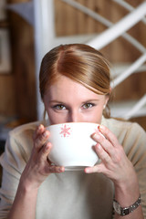 Woman drinking from coffee bowl