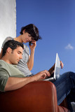 Couple sat outside wuth laptop