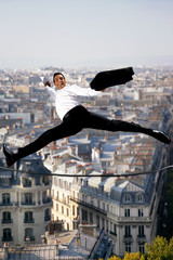Businessman leaping across a tightrope