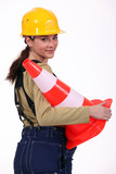 Female builder holding traffic cone