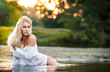 Sexy blonde woman play in lingerie in a river water.