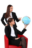 duo of businesswomen with globe