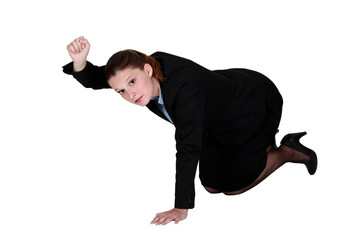 Businesswoman kneeling on the floor and holding up her fist