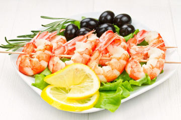 tiger prawns on a skewer with olives