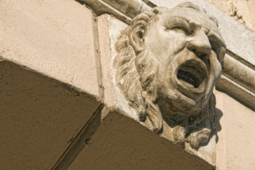 Grotesque mask on an old arch keystone