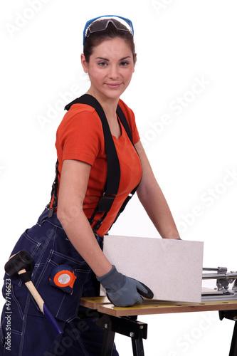 Woman cutting tile