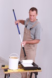 Man applying paint to roller