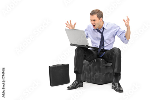 A nervous young businessman screaming on his laptop