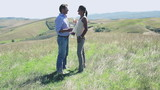 Young couple with wine enjoying panoramic view of Tuscany, crane