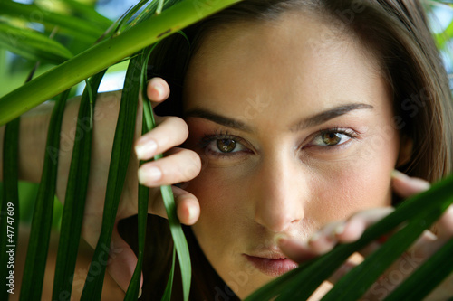 Woman hiding behind leaves