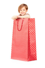 A smiling child posing in a red spotted shopping bag
