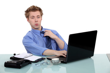 young businessman seated at desk with laptop