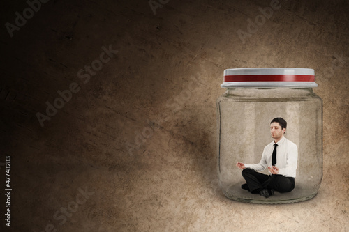 Businessman meditating in jar
