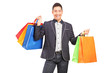A smiling man holding shopping bags
