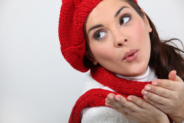 a woman wearing winter clothes is blowing a kiss