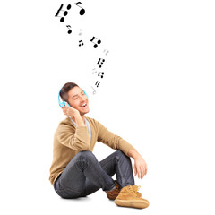 Guy on a floor listening music on headphones and notes around hi