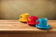 Colorful empty coffee cups on wooden table