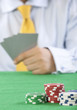 card player with yellow tie  gambling casino chips on green