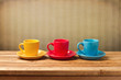 Three colorful coffee cups over vintage background