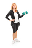 Full length portrait of a mature woman lifting up a dumbbell
